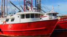 Group Of Commercial Fishing Boats Sitting Idle In Port, Shot Moves Past Boats