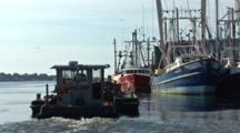 Fuel Boat Moves Past A Group Of Commercial Fishing Boats Sitting Idle In Port