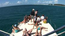 Passengers On Bow Of Boat Searching For Atlantic Spotted Dolphins (Stenella Frontallis) Swim By In Clear Blue Bahamian Water