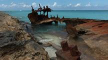 Shipwreck, Aground On A Rocky Shore In The Bahamas, Calm, Clear Water, Boats Travel On Horizon