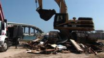 Heavy Construction Equipment Crushes The Remnants Of A Destroyed Boat