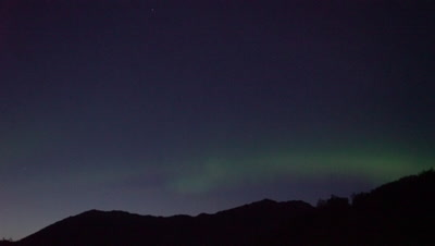 4K Northern Lights in summer sky pan above mountains Aurora Borealis - SLOG2
