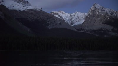 4K NorthernRocky Mountains, snow peaks, lake in foreground at night - NOT Colour Corrected