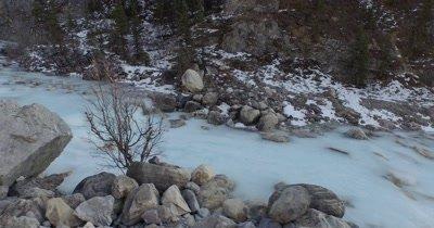 4K Aerial fly along side frozen creek low pass