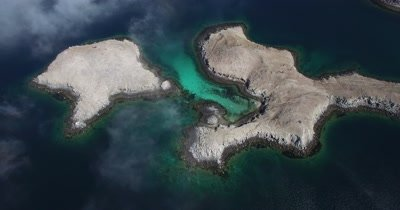 Aerial over cloudy Islands pan up