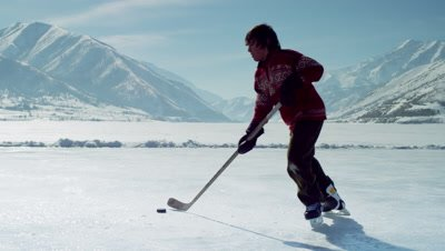 Young boy playing hockey at an outdoor rink.