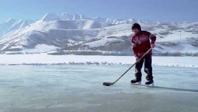 Young boy dribbling a hockey puck toward the goal at an outdoor ice rink.