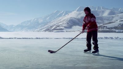 Young boy dribbling a hockey puck at an outdoor ice rink.