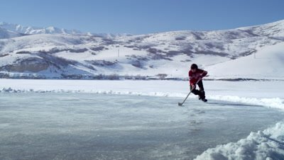 Young boy practicing hockey at an outdoor ice rink.