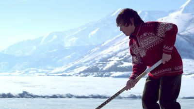 Close up of a boy practicing hockey at an outdoor ice rink.