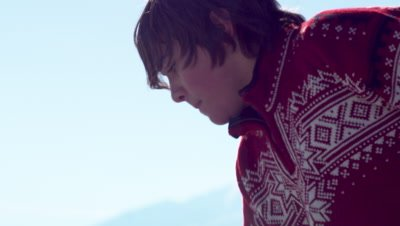 Young boy in a red sweater practicing hockey outdoors.