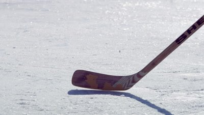 Close-up of a young boy dribbling a hockey puck in a circle.