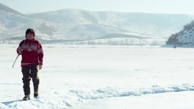 Young boy in a red sweater walking onto a frozen pond to play hockey.