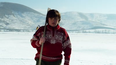 Young boy with a hockey stick walking onto a frozen pond.