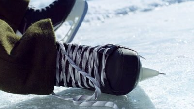 Close up of a hockey skate being tied at an outdoor rink.