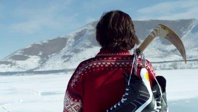 Youth walking across a frozen lake with hockey gear.