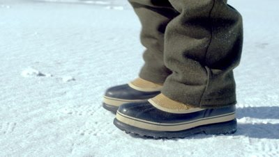 Boots walking across the snow-covered ground.