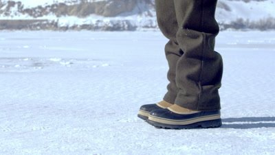 Snow boots walking across the snowy ground.