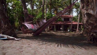 Dolly shot of a man enjoying himself on a hammock