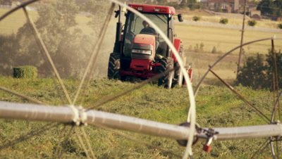 Shot of approaching hay baler taken from behind the wheel irrigation system