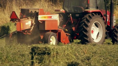 Shot of a farmer operating a hay baler as he goes around the field