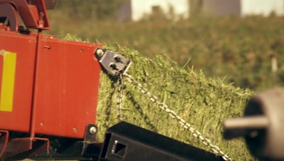 Medium shot of a hay baler dropping a bale of hay on the ground