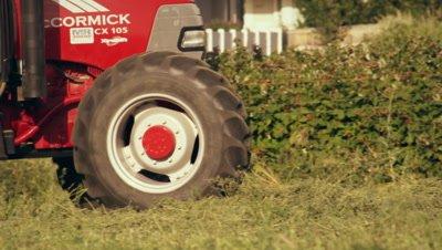 Medium shot of a farmer driving a hay baler as he goes around the farm