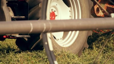 Medium shot of a hay baler as seen from behind a wheel irrigation system