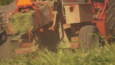 Shot of a square hay baler going around the farm as it turns piles of hay into bales