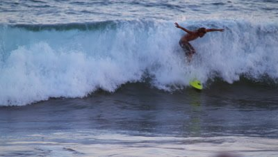 Shot of a young male surfer surfing along the coast in Costa Rica