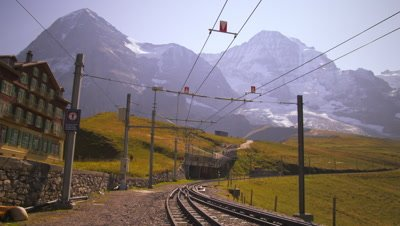 Swiss railcar full of passengers passes hotel and approaches Alps