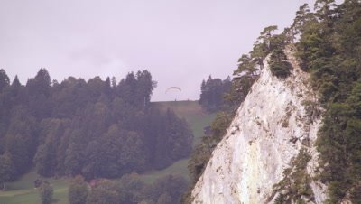 Long distance shot of a lone paraglider taking off from a hill
