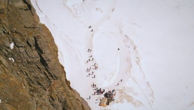 Tilting shot of several people trekking to the Swiss Alps