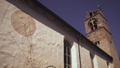 Static shot of an old church with a sundial on its wall in Switzerland