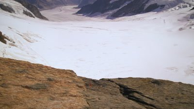 Tilting shot of snow on top of the alpine mountain range in Switzerland