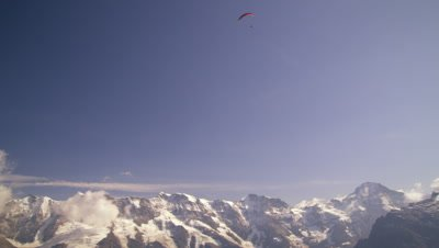 Long distance shot of a paraglider hovering above the Swiss alps