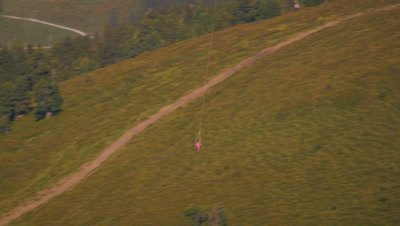 Long distance shot of a helicopter airlifting an object and flying over the hills in Switzerland