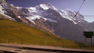 Pan of Swiss alps, train tracks, and hotel