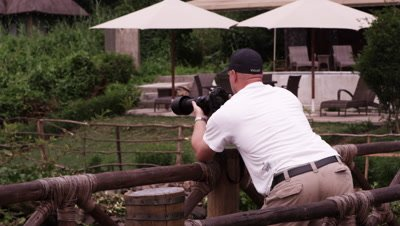 White man takes photos over wooden fence
