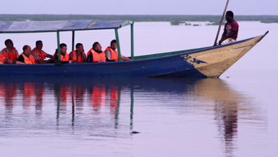 Tourists photograph hippos from boat