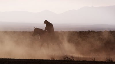 Slow motion silhouette shot of two cowboys out in the open range