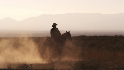 Slow motion silhouette shot of a cowboy riding a hourse in a circle