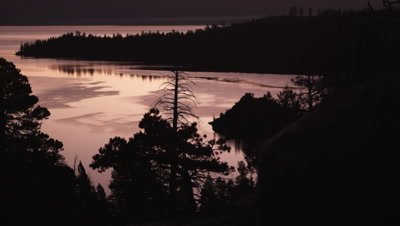 Static shot of a Emerald Bay, Lake Tahoe, California at sunset with silhouetted foreground trees.