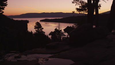 Static shot of Lake Tahoe at sunset with silhouetted trees and flowing river in the foreground