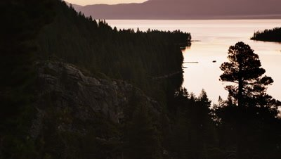 Static shot of a cliff overlooking Lake Tahoe at sunset.