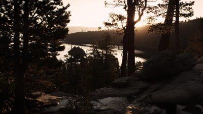 Dark shot of sun peaking through trees over water andÊstream near Lake Tahoe, California.
