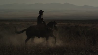 Slow motion static shot of cowboy riding a horse that is turning around