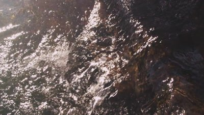 Slow motion shot of water flowing over rocks.