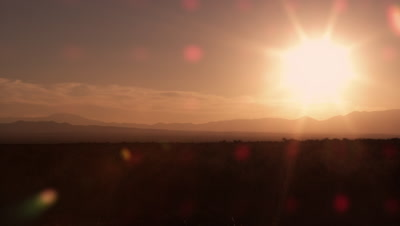 Slow motion shot of cowboy galloping in front of sunrise.