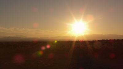 Slow motion shot of cowboys galoping at sunset.